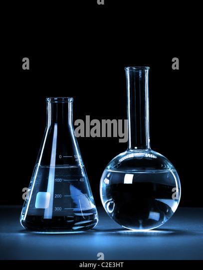 Laborglas mit blauem Licht auf dunklem Hintergrund - mit Beschneidungspfad Stockbild