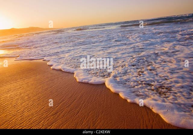 Welle bei Sonnenuntergang am Strand von Las Canteras in Spanien Stockbild