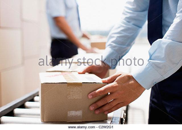 Arbeiter nehmen Box von Förderband im Bereich Versand Stockbild