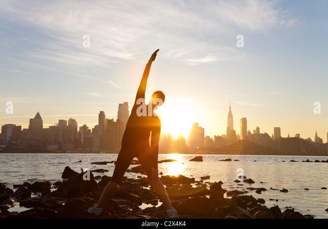 Ein Frau Läufer stretching in einer Yogaposition vor der Skyline von Manhattan, New York City, USA, am Dawn Stockbild