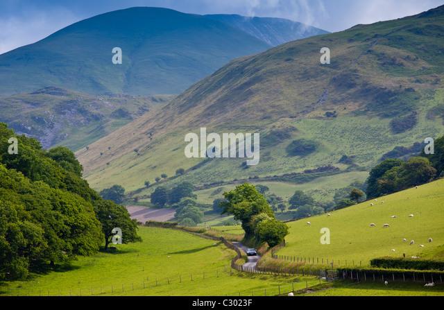 Auto fahren auf kurvenreichen Straße durch malerische Tal bei Llanfihangel, Snowdonia, Gwynedd, Wales Stockbild