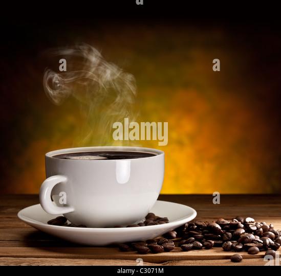 Tasse Kaffee mit Kaffeebohnen auf einem schönen braunen Hintergrund. Stockbild