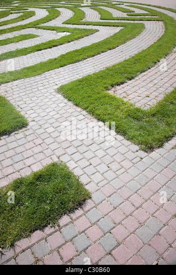 Erhöhte Ansicht des Anfangs wie ein Labyrinth mit einem gepflasterten Gehweg und Rasen Grenzen. Vertikale erschossen. Stockbild