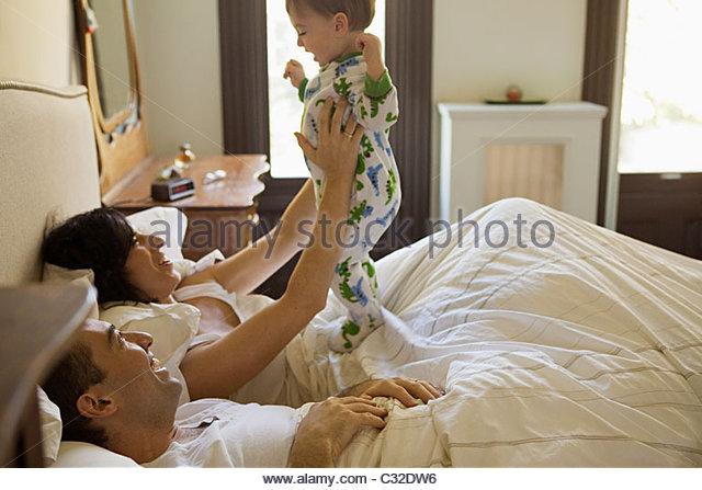 Eltern und Baby Sohn mit einer Lüge in Stockbild