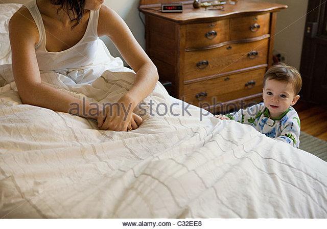 Mutter saß im Bett mit einer Lüge in mit Sohn Stockbild