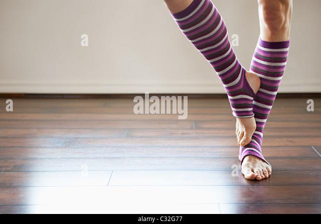 Frau trägt stripey stehen auf einem Bein Stulpen Stockbild