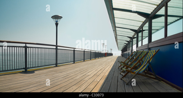 Leere Liegestühle aufgereiht auf einem Steg direkt am Meer Stockbild