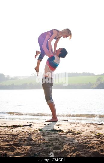 Mann heben Mädchen am Sommerstrand, liebevolle Stockbild