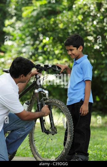 Vater und Sohn zusammen Fahrrad reparieren Stockbild