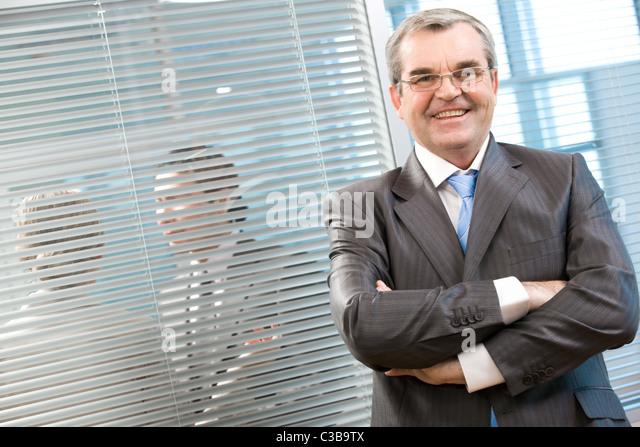 Bild der Führungskraft lächelnd in die Kamera auf Grund der Jalousie Stockbild
