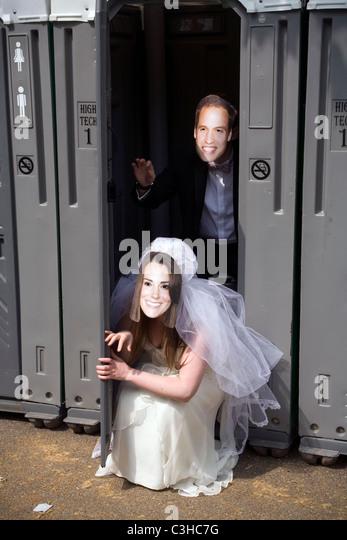 Paar mit den Masken von Prinz William und Kate Middleton in einer Toilette, London England, UK Stockbild