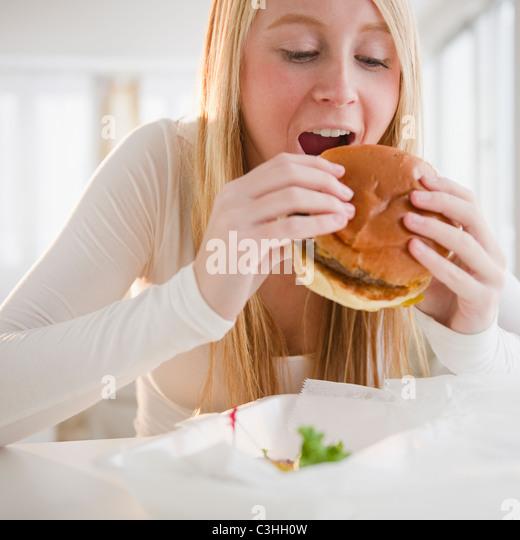 Frau Hamburger Essen Stockbild