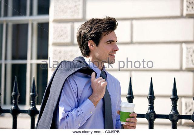 Ein Geschäftsmann gehen, halten Sie ein heißes Getränk Stockbild