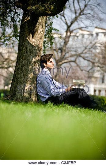 Ein Geschäftsmann an einen Baum gelehnt, der ein Buch hält Stockbild
