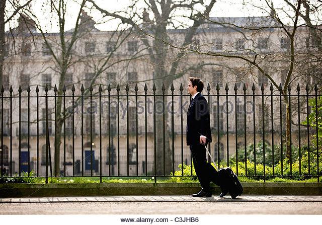 Ein Geschäftsmann seinen Koffer ziehen Stockbild
