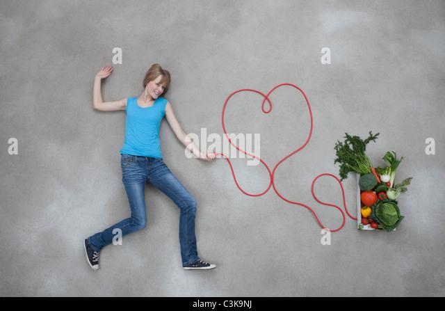 Mitte Erwachsene Frau an Gemüse Box angeschlossen halten Elektrokabel Stockbild
