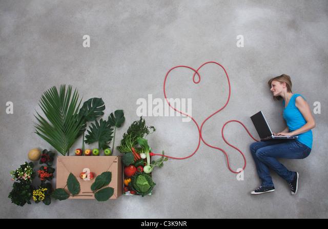 Mitte Erwachsene Frau an Gemüse Box angeschlossen mit Laptop und Elektrokabel Stockbild