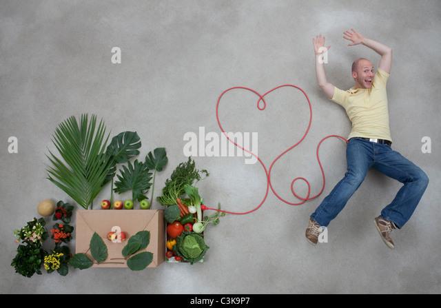 Junger Mann liegend von Obst und Gemüse im Zusammenhang mit Stromkabel Stockbild