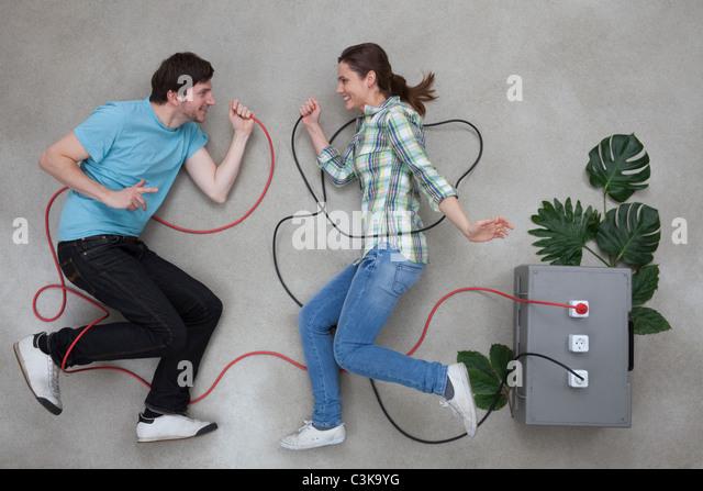 Mann und Frau halten Kabeldraht und Blick auf einander, Lächeln Stockbild
