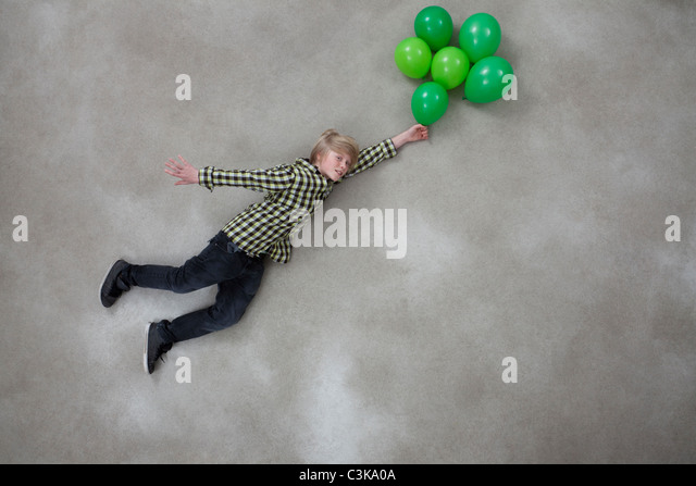 Junge mit Luftballons auf grauem Hintergrund Stockbild