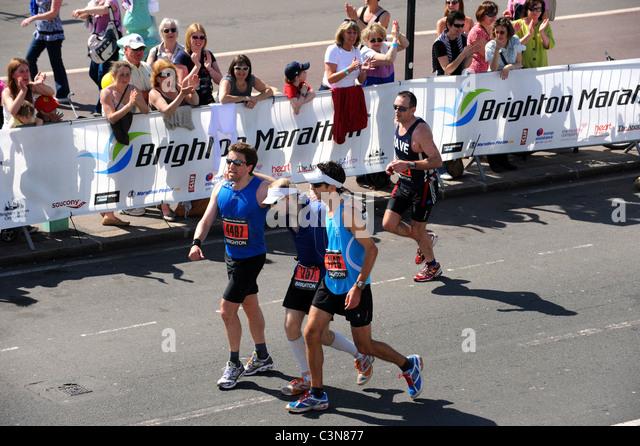 Brighton Marathon 2011 - gegenseitig erschöpften Läufer die Ziellinie Stockbild