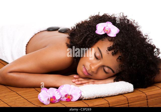 Glückliche Frau Gesundheit Day Spa mit hot-Stone massage-Behandlung Verlegung in weißes Handtuch auf Bambus Stockbild