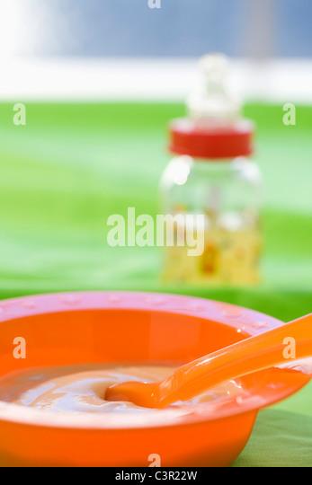 Babynahrung in Schüssel mit Baby-Flasche im Hintergrund Stockbild