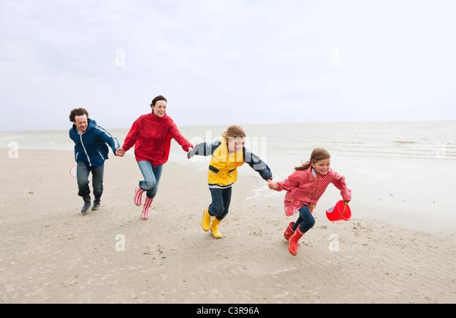 Deutschland, St. Peter-Ording, Nordsee, Familie Hand in Hand und laufen am Strand Stockbild