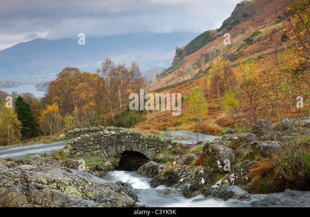 Barrow Beck fließt unterhalb der malerischen Ashness Brücke, Nationalpark Lake District, Cumbria, England. Stockbild