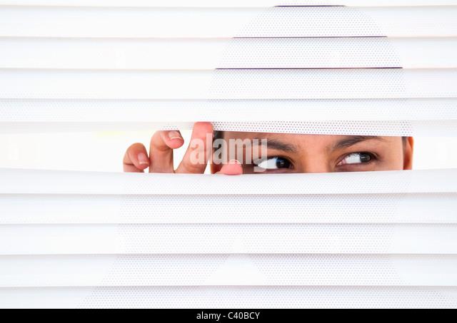 Frau schaut durch Jalousien Stockbild