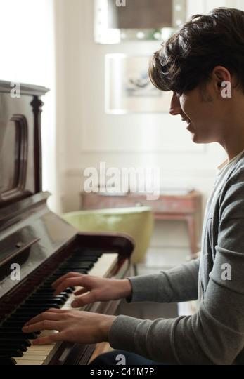 Junger Mann spielt Klavier Stockbild