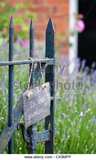 Im Garten geschrieben in Kreide auf Schiefer, hängen an einem Eingangstor Stockbild