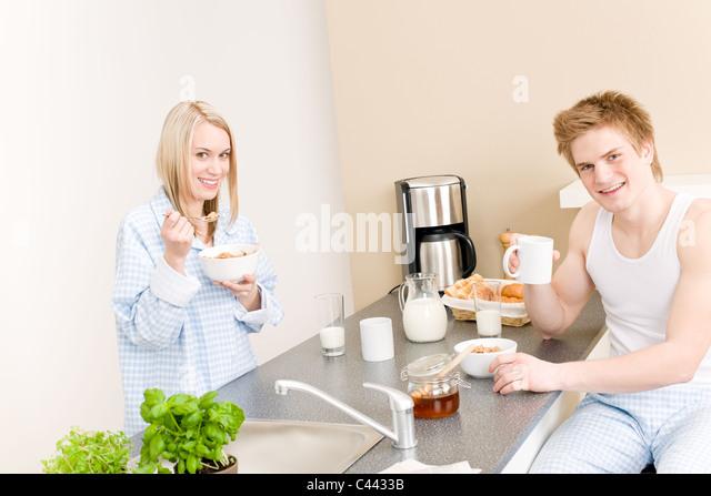 Glückliches Paar Frühstück essen Getreide Kaffee trinken in Küche Stockbild