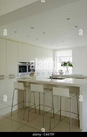 Weiße moderne Küche mit Corian Arbeitsplatten, Barhockern und Einbauschränke Stockbild