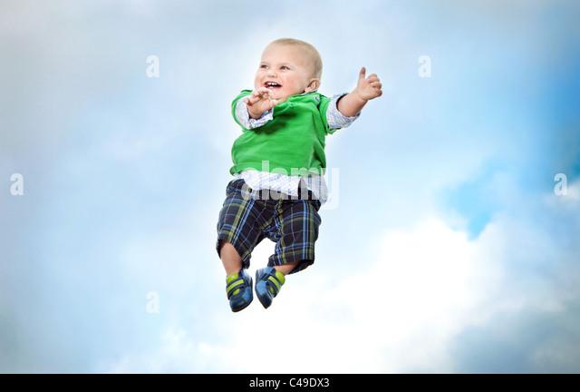Einen kleinen Jungen in trendige Kleidung fliegen in der Luft vor einem blauen Himmel. Stockbild