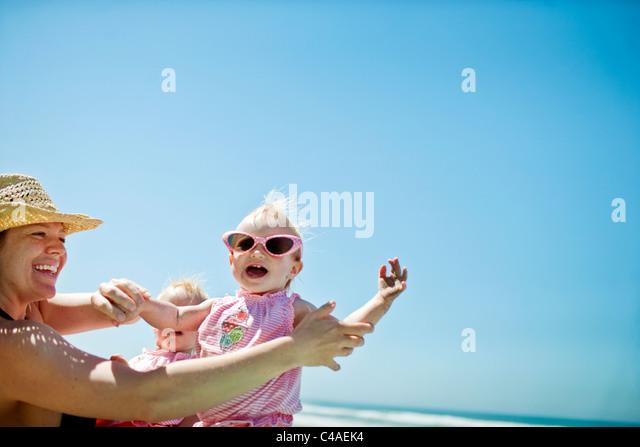 Mutter mit Tochter am Strand spielen Stockbild