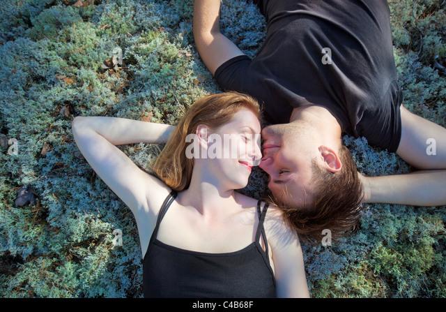 Junges Paar ruht auf dem Rasen im Wald. Stockbild