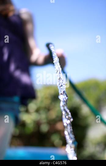 Mädchen mit einer Schlauchleitung Stockbild