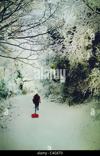 Mädchen im Schnee mit Schlitten laufen Stockbild