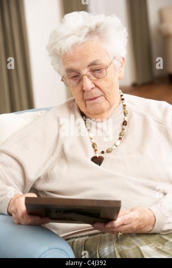 Senior Woman Looking At Foto im Rahmen Stockbild