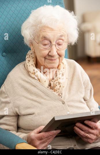 Traurig Senior Woman Looking At Foto im Rahmen Stockbild