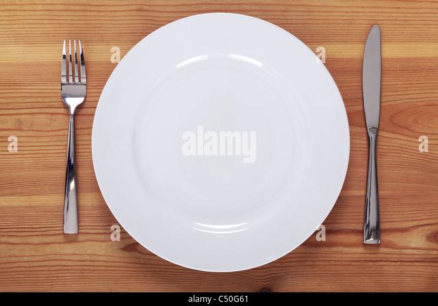 Foto von einem leeren weißen Teller mit Messer und Gabel auf einem rustikalen Holztisch. Stockbild