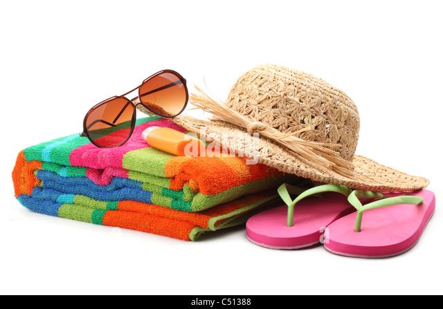 Strandzubehör mit Strohhut, Handtuch, Flip Flops und Sonnenbrillen. Isoliert auf weißem Hintergrund. Stockbild