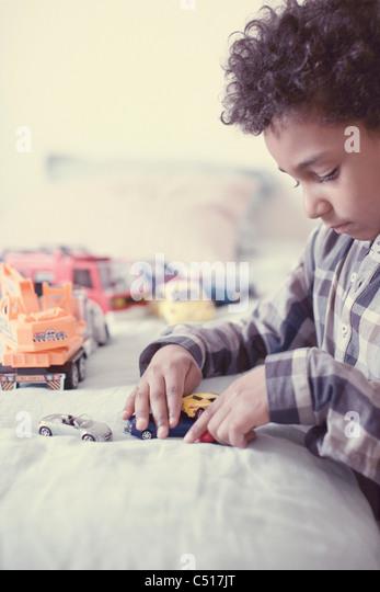 Kleiner Junge spielt mit Spielzeug-Autos Stockbild