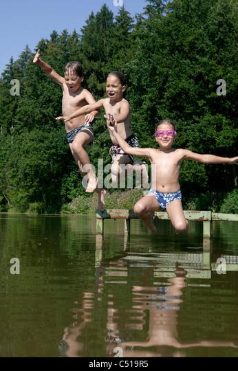 drei Kinder springen in See Stockbild