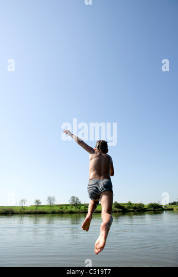 kleiner Junge in den See springen Stockbild