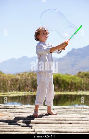 Junge spielt mit einem Blase Wand an einem pier Stockbild