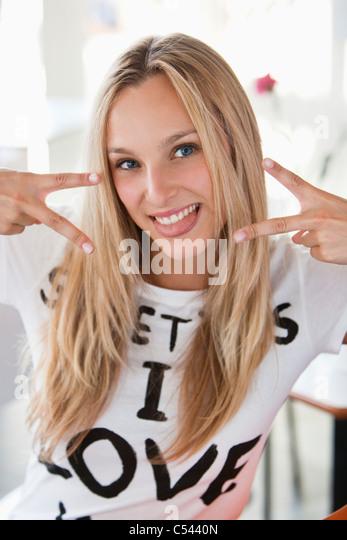Porträt einer schönen Frau mit Peace-Zeichen in einem café Stockbild