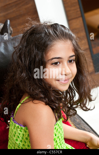 Schönes ethnische Mädchen saß auf Sofa wegschauen Stockbild