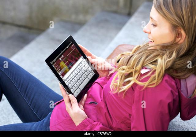 Ansicht einer kaukasischen jungen Frau im Chat mit IM (Instant Messaging) app app auf dem iPad 2 durch drahtlose Stockbild